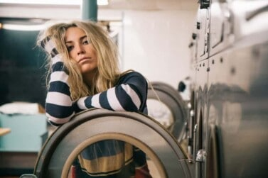 blonde woman leaning on laundromat washer door looking tired