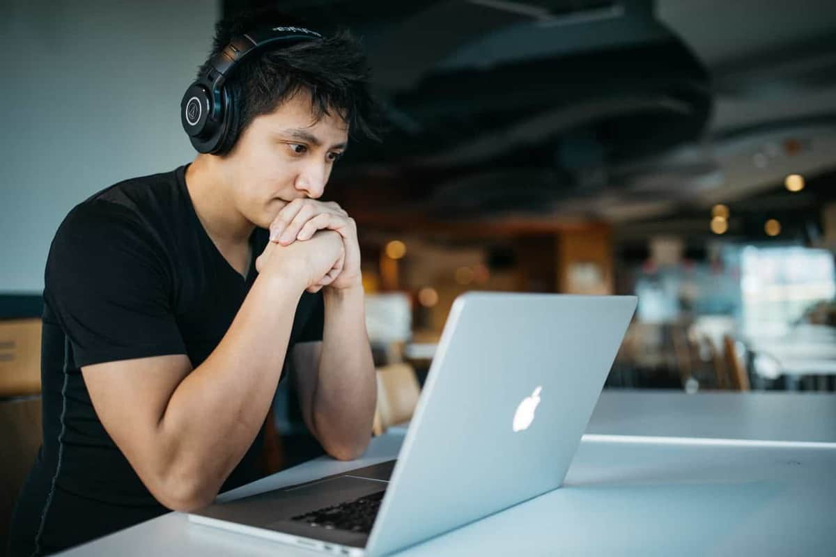 man with headphones on staring at laptop screen