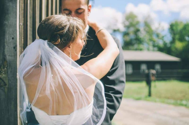 newlywed couple hugging outside a lodge for wedding photos