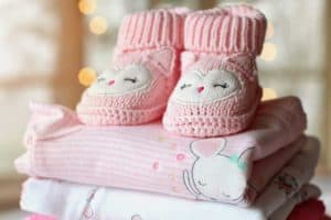 pink knitted baby boots on stack of folded baby blankets