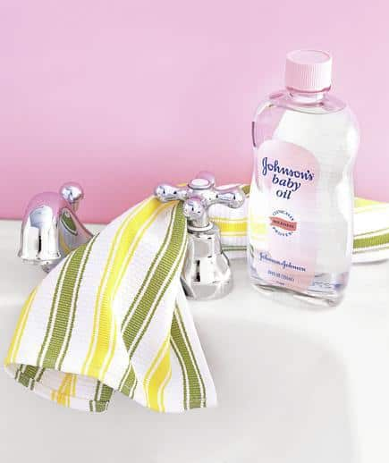 yellow and green striped towel hanging over a bathroom faucet with a bottle of baby oil nearby as a faucet bathroom cleaning hack