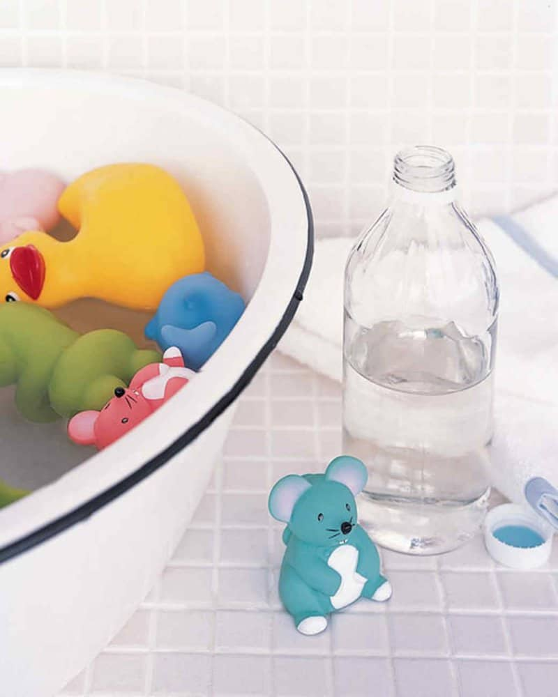 white bowl with baby bath toys soaking in water with an open bottle of vinegar on the counter nearby
