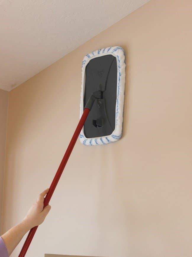 using a large microfiber mop to clean the wall as a bathroom cleaning hack