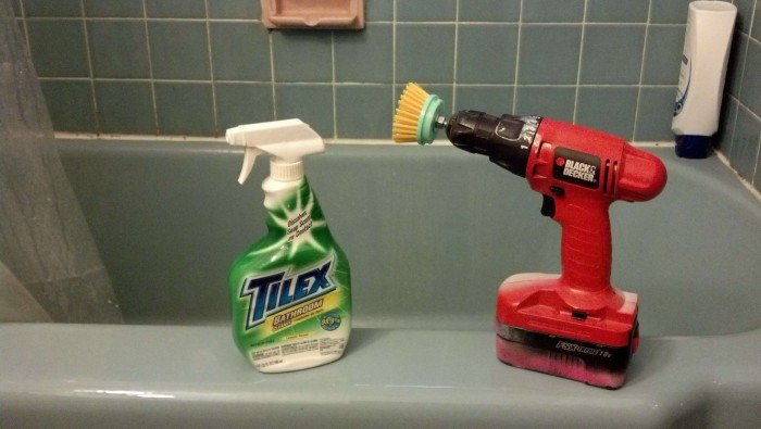 drill and a bottle of tilex sitting on the edge of a bathtub in preparation for deep bathroom cleaning