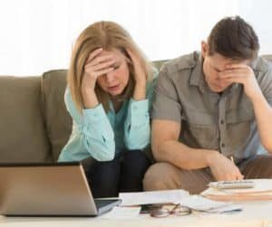 older couple sitting on couch holding heads and looking stressed over a pile of papers with calculator and laptop