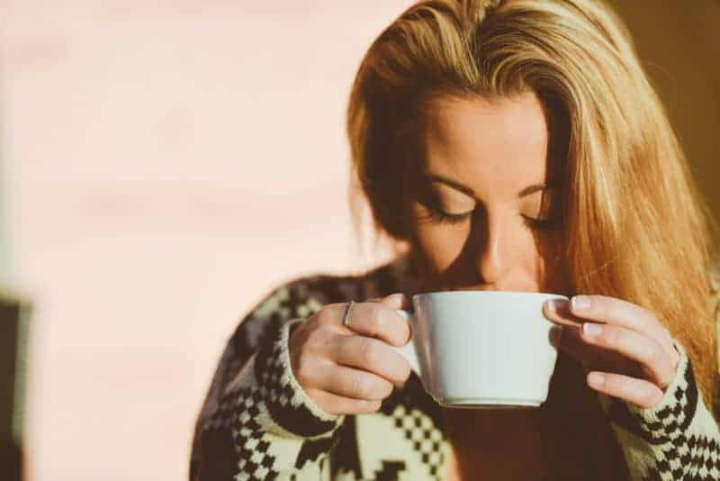 alone woman sipping coffee from white mug