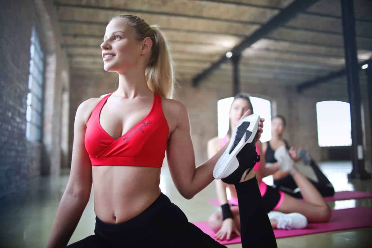 blond woman in workout clothes smiling while doing yoga stretches