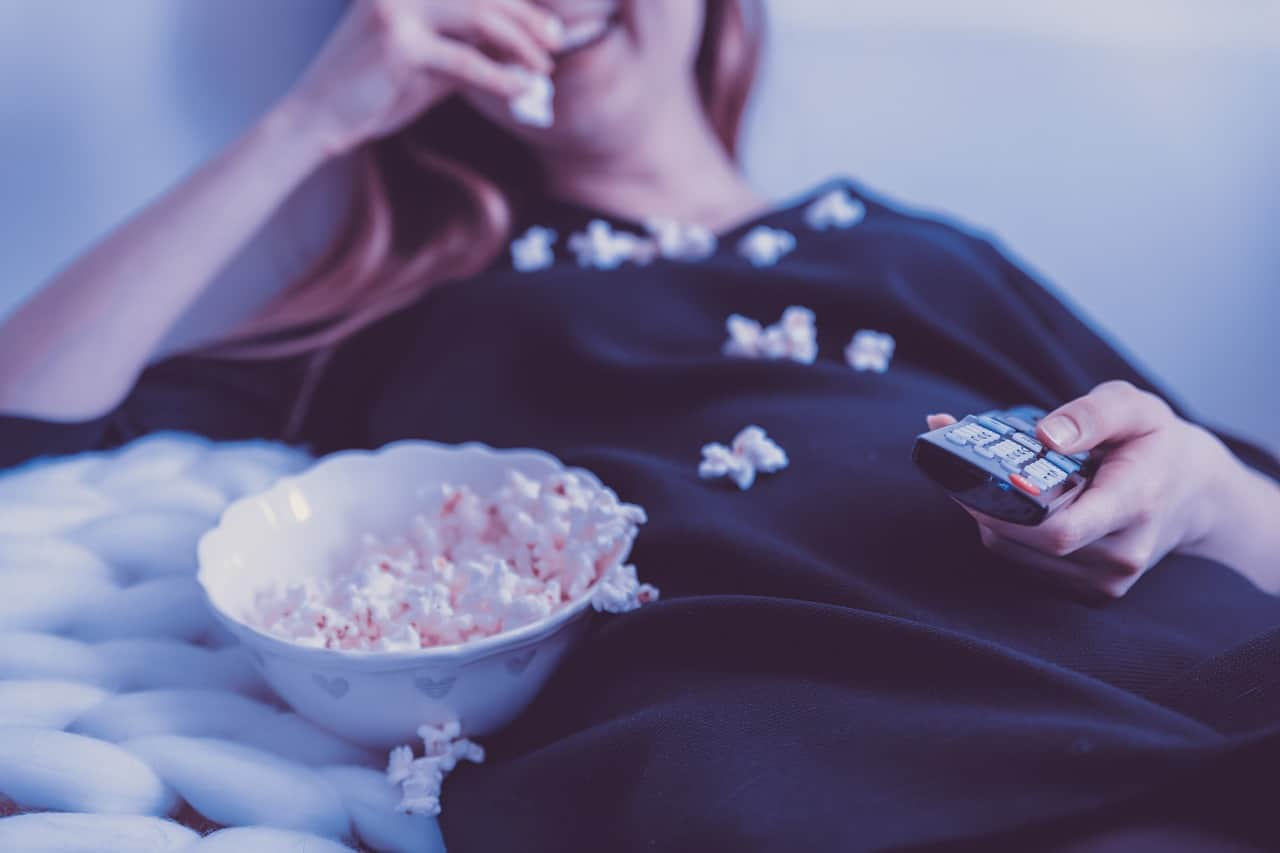 woman smiling while eating popcorn and holding tv remote