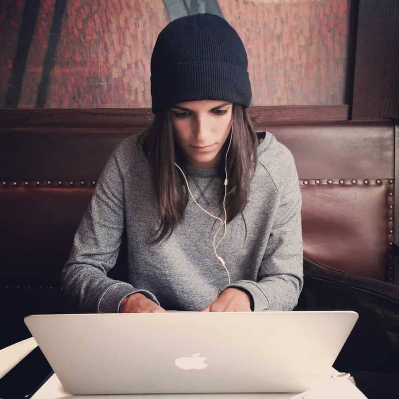 young woman in black hat working on laptop with headphones in