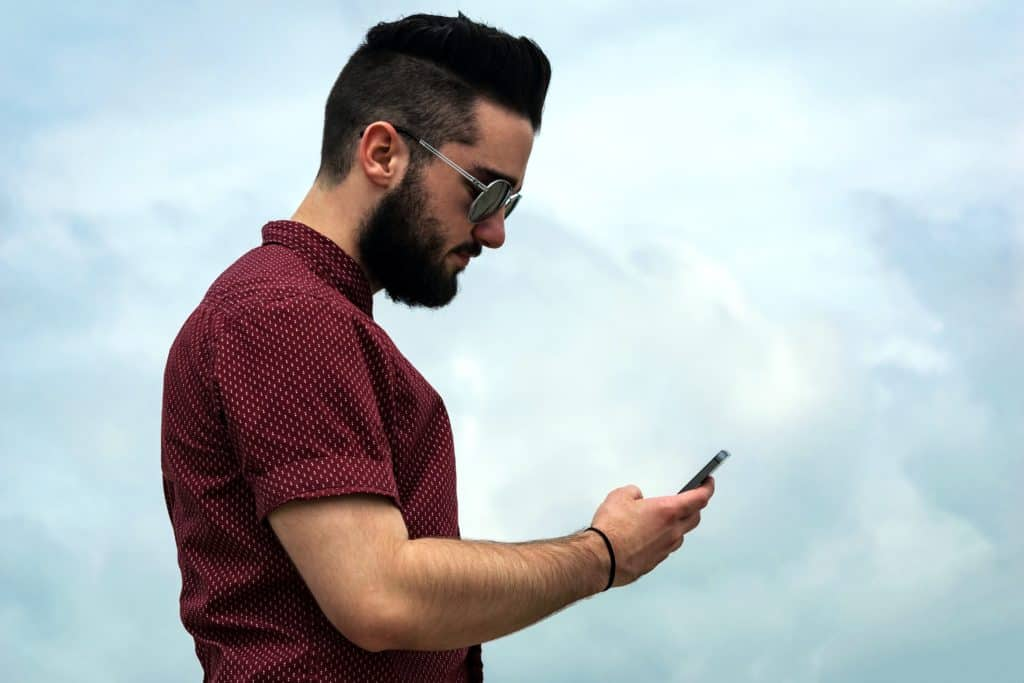 young man in sunglasses looking at smartphone