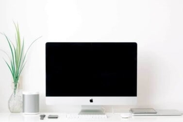 iMac desktop computer on white desk with tech accessories and a thin green plant nearby