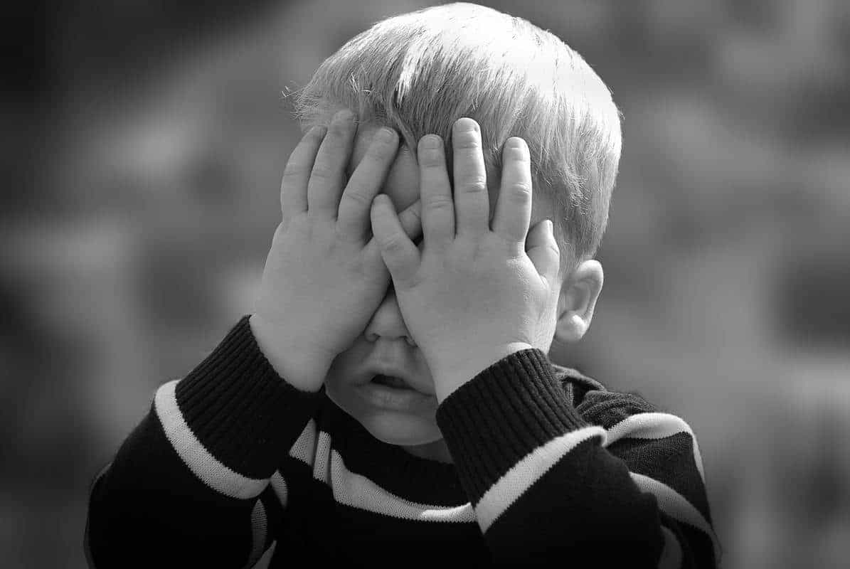 young boy holding hands over eyes in black and white photo