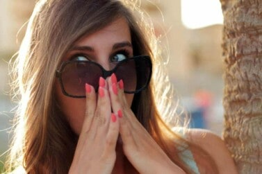surprised woman holding hands to mouth with wide eyes behind her sunglasses