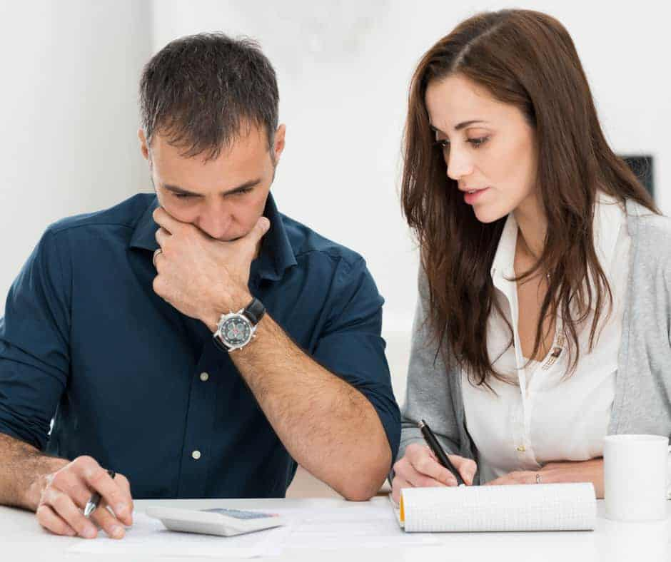 couple calculating and budgeting with focused looks on their faces
