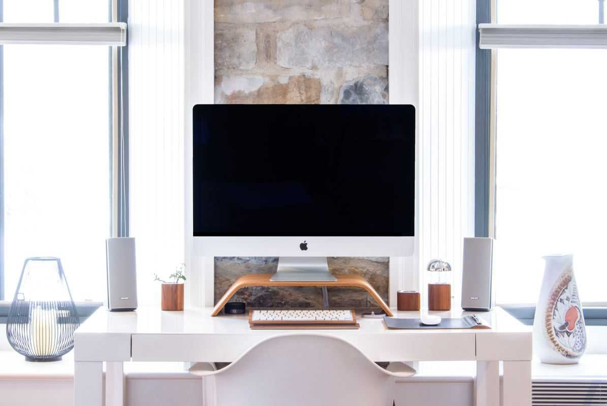 iMac desktop computer on a white desk in a brightly lit room