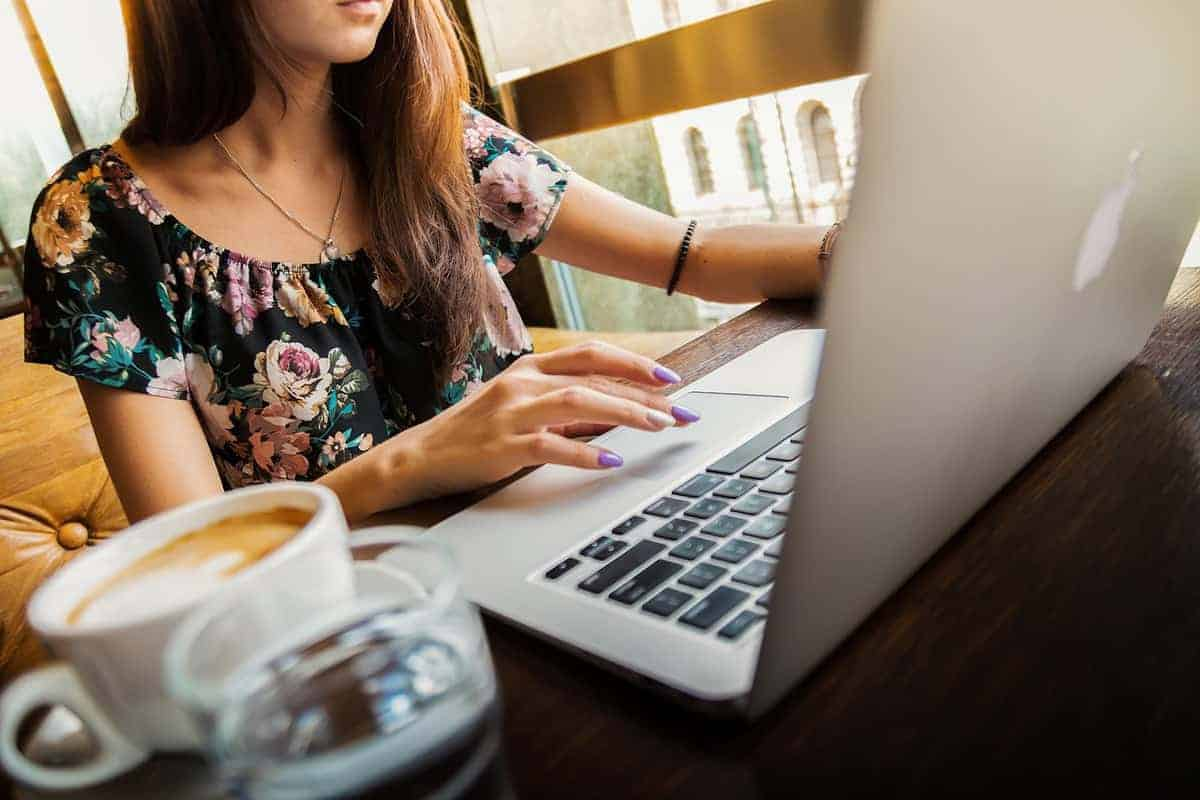 woman working on laptop near window with cup of coffee