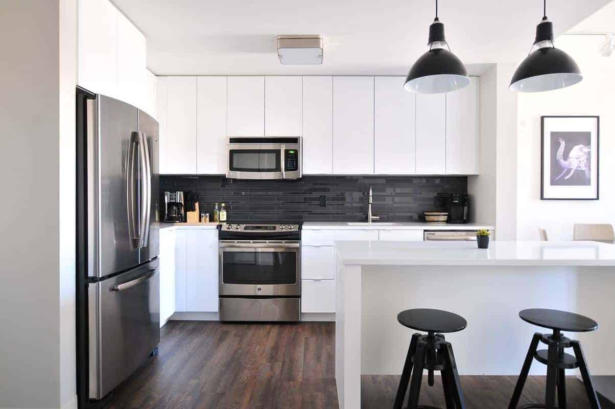 clean and empty white kitchen with stainless appliances