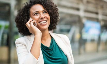 woman in business casual smiling, talking on phone