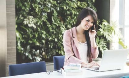 brunette in business dress smiling while talking on phone, working on laptop, stack of books nearby