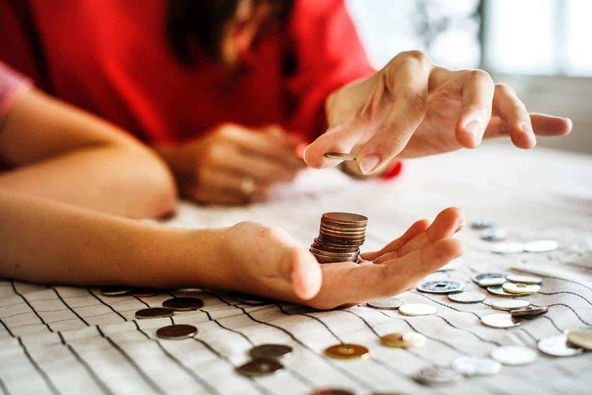 people counting coins stacked in palm