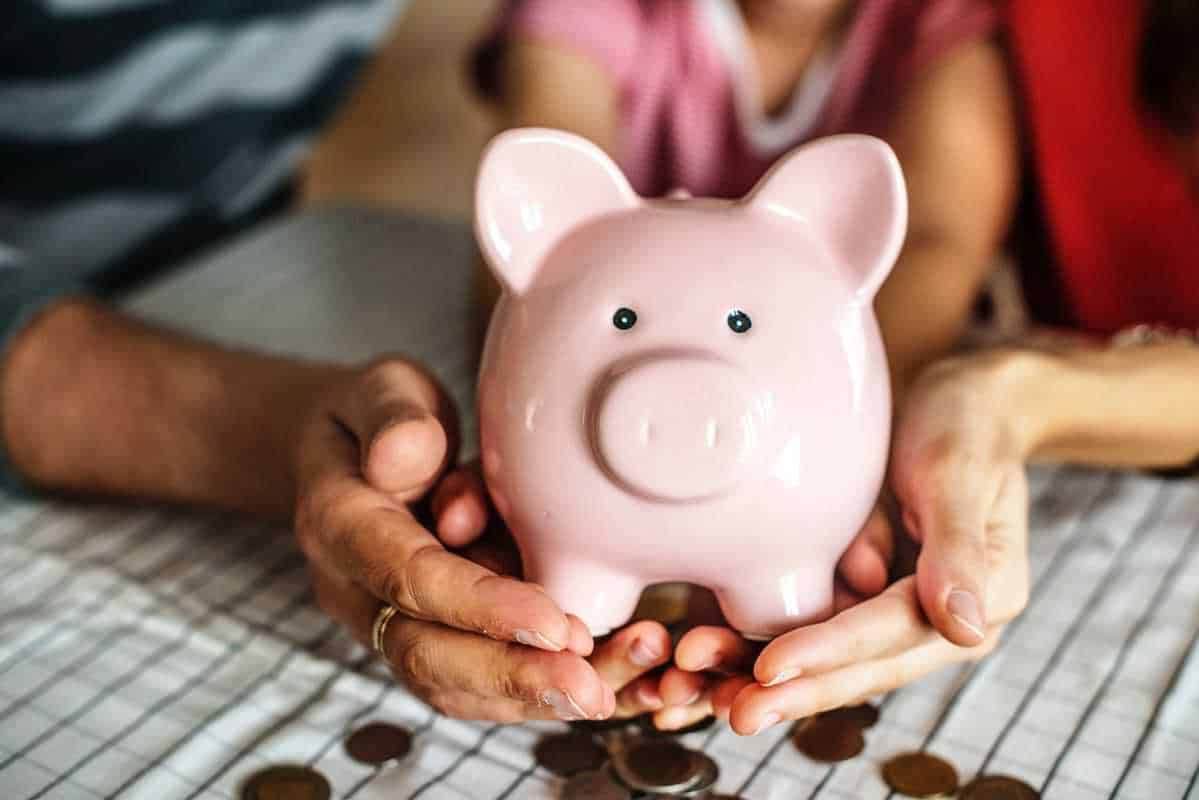 multiple hands holding up pink piggy bank with coins beneath it