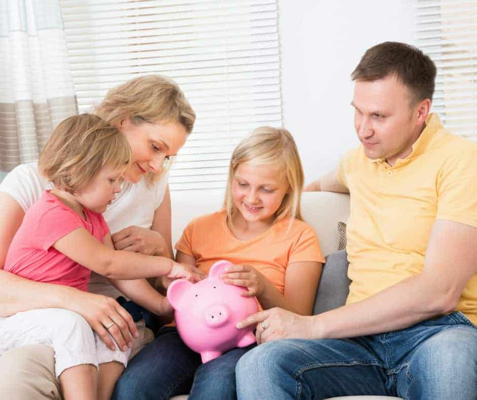 Family of 4 saving money into a pink piggy bank.