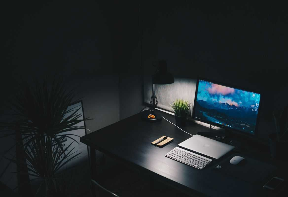dark room with solitary small desk lamp and a desktop computer with laptop and accessories