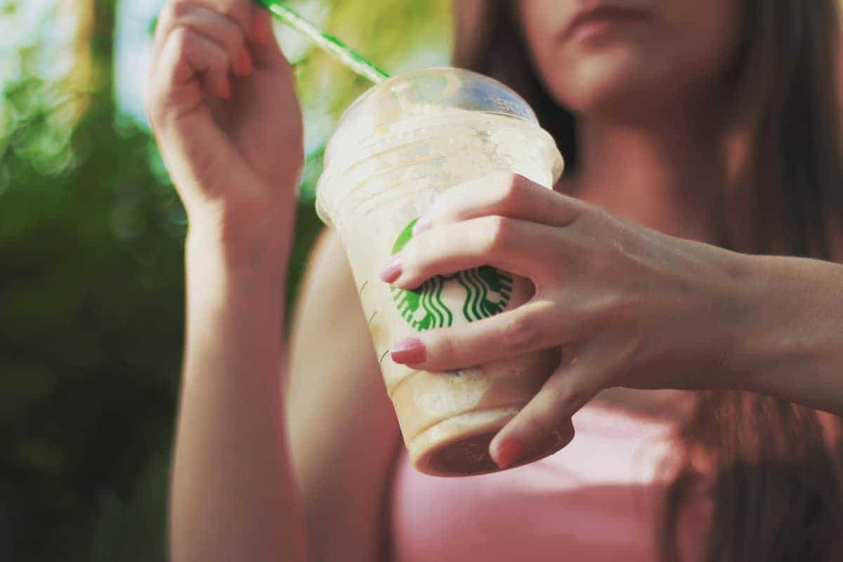 woman pulling straw out of a Starbucks up