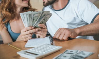 Man and woman sitting at table budgeting their money