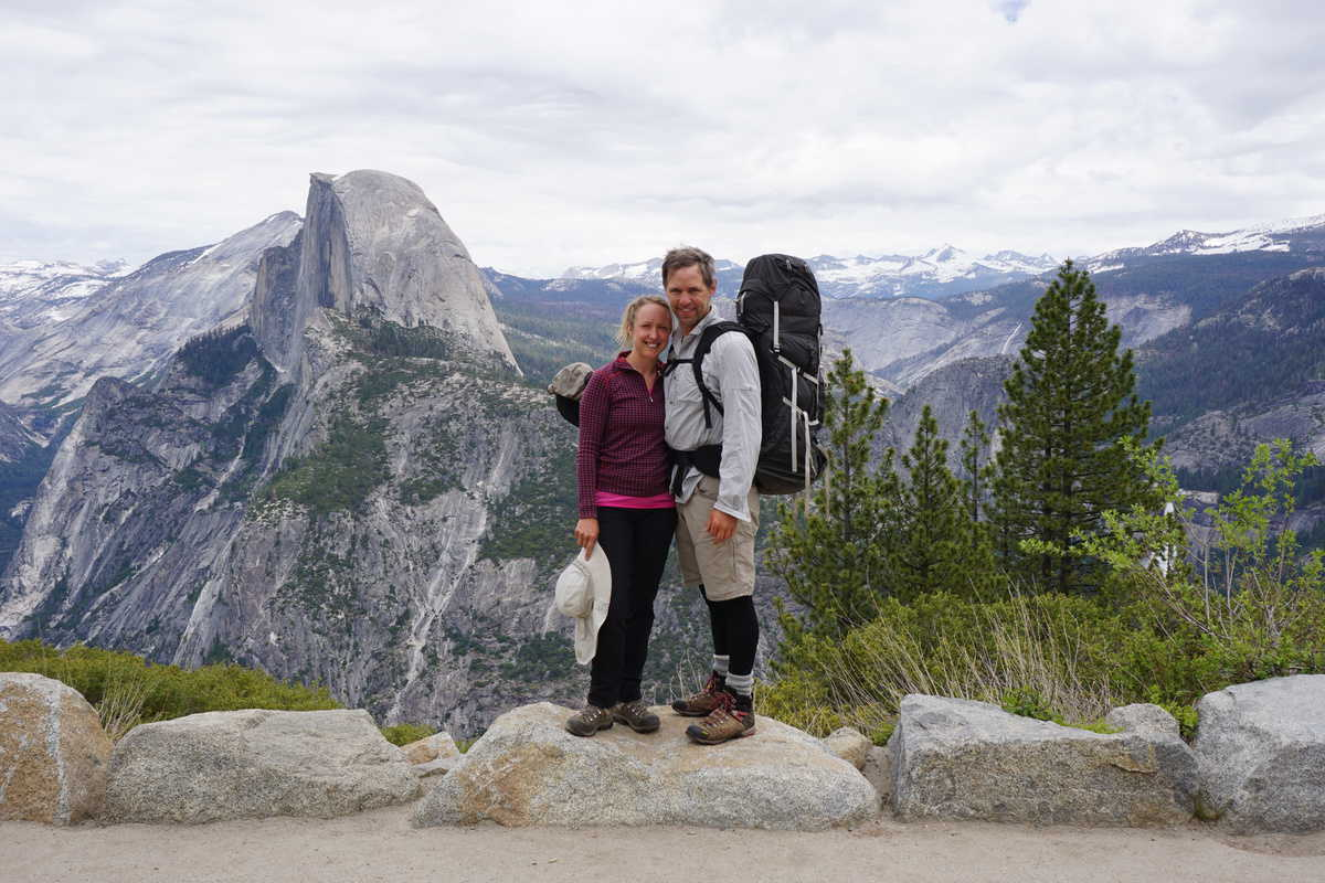 Couple hiking standing on a rock with a beautiful mountain background