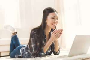 Happy woman lying on carpet and clapping hands in front of laptop computer because she is using free internet