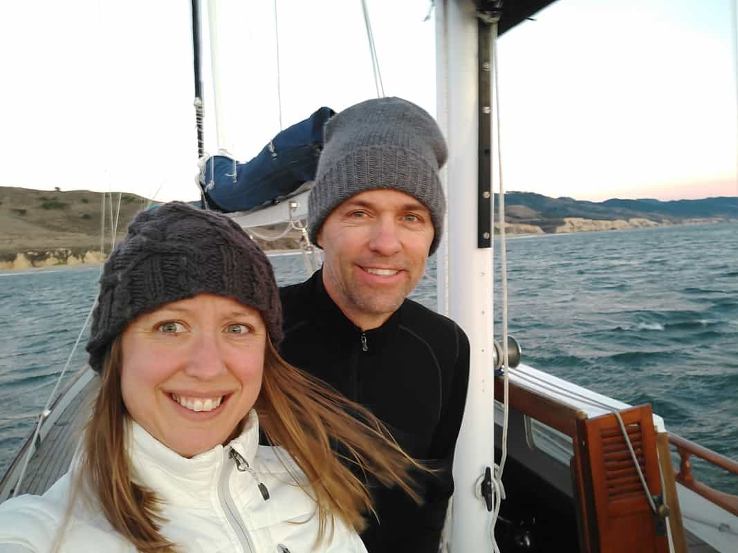 Couple smiling while they sail on their sailboat on the ocean