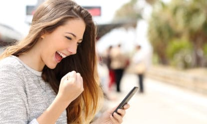 young woman outside with phone in hand happily making a fist and smiling at phone