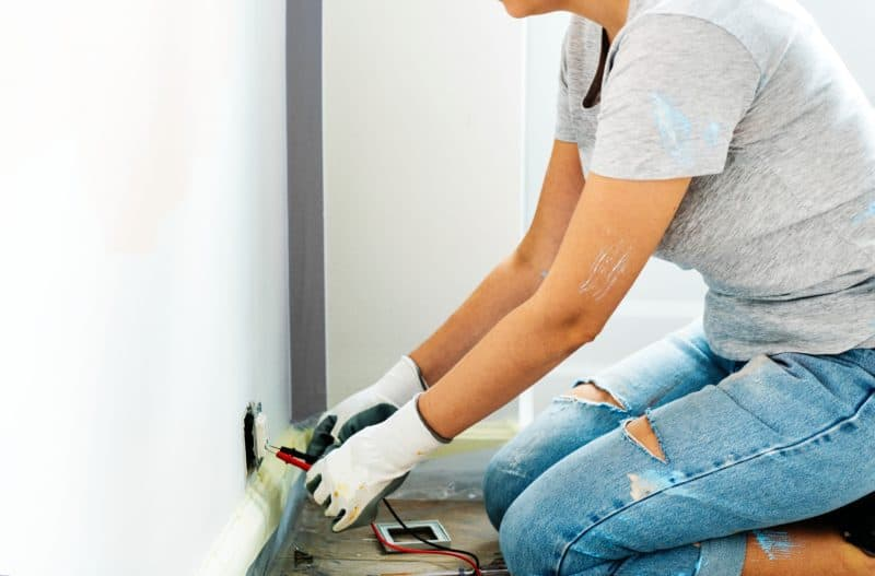 woman wearing work clothes and gloves while testing an electrical outlet during home repairs
