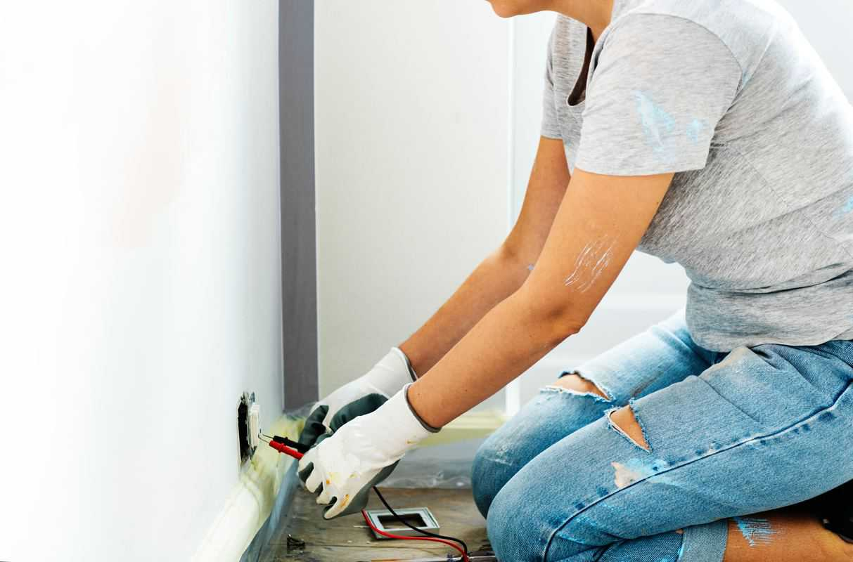 Woman kneeling checking an electrical outlet with prongs.