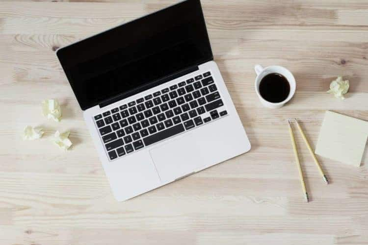 laptop with wadded papers, cup of coffee, and pencil and pad on a light wood tabletop