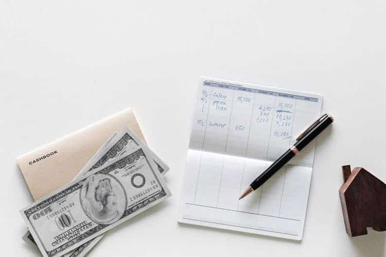 checkbook register with pen, cash, and a wood toy house on white table