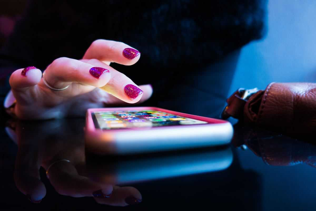 woman's hand operating a smart phone laying on a table