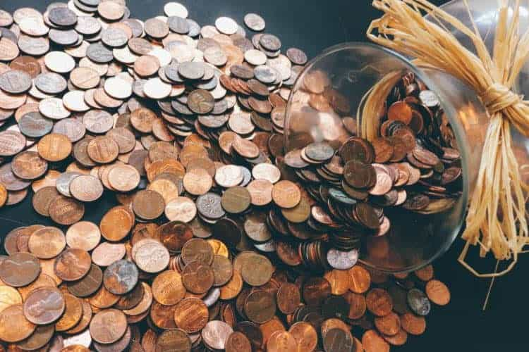 A jar of pennies spilled on a table