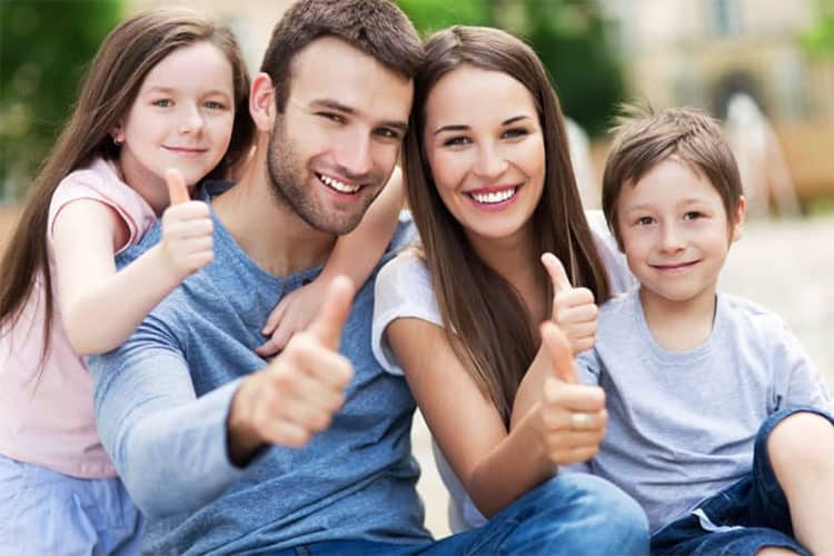 Smiling family giving the camera a thumbs up