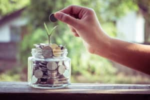 hand putting coins into glass jar with seedling growing out of it representing building a successful financial plan