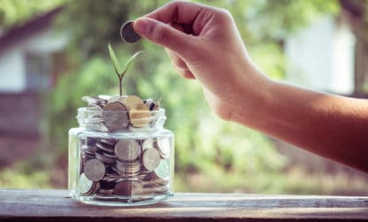 hand putting coins into glass jar with seedling growing out of it