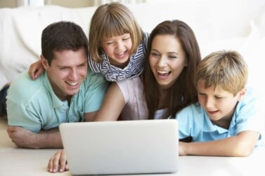 Young parents, with children, on laptop computer making money with Swagbucks
