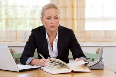 successful young businesswoman sitting at desk with laptop computer looking over blogging laws
