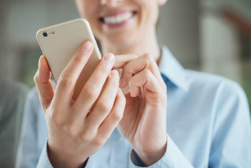 Beautiful smiling young woman using a smart phone to do mystery shopping job and earn extra money