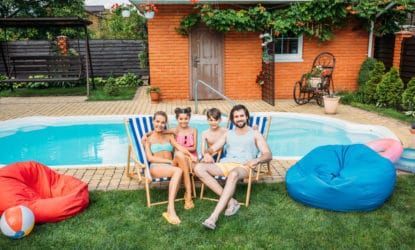 Smiling family sitting in beach chairs by the pool at the Airbnb they rented
