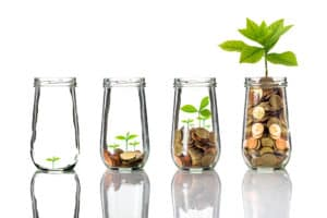 Gold coins and seed in clear bottle on white background,Business investment growth concept