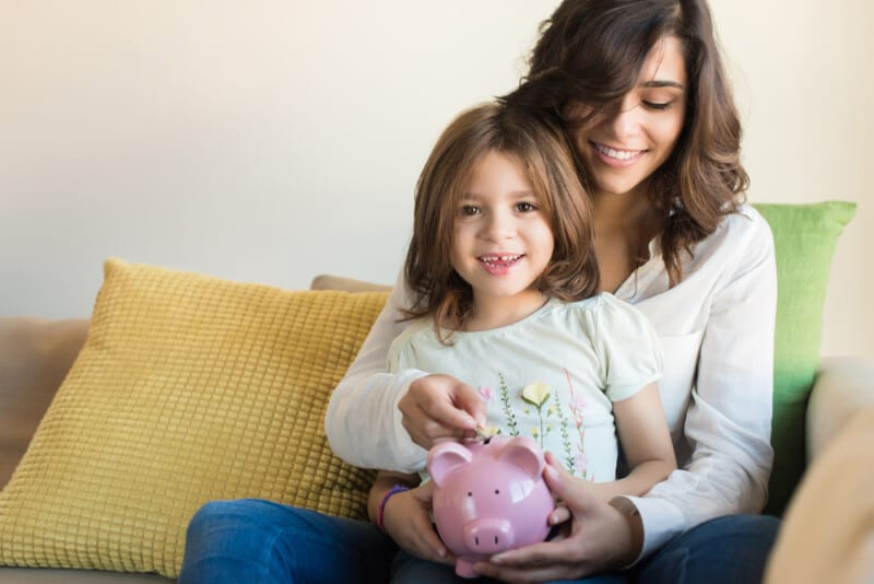 mom teaching daughter to save monthly to avoid living beyond your means