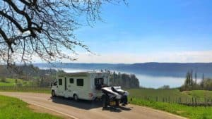 RV towing bikes on a road overlooking a vineyard and a lake surrounded by mountains