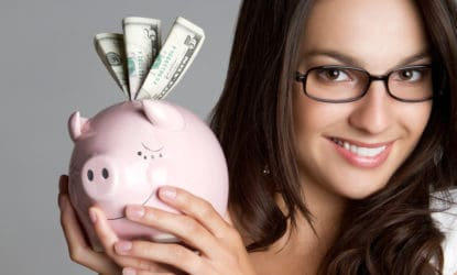 Smiling girl holding piggy bank money after saving using Trim